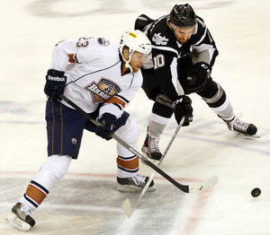Photo - Barons'  Linus Omark and San Antonio's Jon Matsumoto battle for the puck during their game at the Cox Convention Center in Oklahoma City, Tuesday November 12, 2013. Photo By Steve Gooch, The Oklahoman
