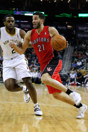 Photo - Toronto Raptors guard Greivis Vasquez (21) drives against New Orleans Pelicans forward Darius Miller (2) during the first half of an NBA basketball game in New Orleans, Wednesday, March 19, 2014. The Raptors won 107-100. (AP Photo/Jonathan Bachman)
