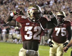 Photo - Florida State running back James Wilder Jr. (32) celebrates after scoring a touchdown against Miami during the second quarter of an NCAA college football game Saturday, Nov. 2, 2013, in Tallahassee, Fla. At right is offensive linesman Cameron Erving (75). (AP Photo/Phil Sears)