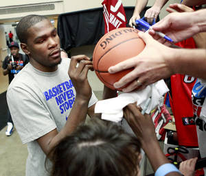Photo - Kevin Durant signs autographs before the US Fleet Tracking Basketball Invitational at the Cox Convention Center in Oklahoma City Sunday, Oct. 23, 2011. Photo by John Clanton, The Oklahoman