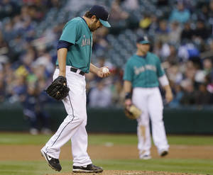 Seattle Mariners starting pitcher Joe Saunders reacts on the mound in the fourth inning of a baseball game against the Texas Rangers, Friday, May 24, 2013, in Seattle. (AP Photo/Ted S. Warren)
