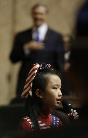 Photo - Gov. Jay Inslee looks on as Lena Hou sings the national anthem, during a joint session of the Legislature, Wednesday, Jan. 16, 2013, in Olympia, Wash. shortly after Inslee was sworn in as governor. (AP Photo/Ted S. Warren)