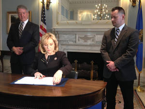 Photo - Dr. Bob Sommers, secretary of education and workforce development, (left) and Mustang Public Schools employee Jonathon Atchley (right) watch as Gov. Mary Fallin prepares to sign an executive order supplementing common core standards on December 4, 2013. Photo by Graham Lee Brewer, the Oklahoman. <strong></strong>