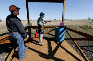 Photo - Tony Greenberg, Oklahoma City, right, prepares to shoot as John Russell scores at Quail Ridge Sporting Clays on Wednesday, Feb. 13, 2013 in Norman, Okla.   Photo by Steve Sisney, The Oklahoman