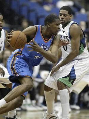 photo - Oklahoma City Thunder forward  Kevin  Durant, left, drives against Minnesota Timberwolves forward Rodney Carney during the second half in an NBA basketball game, Sunday, March 22, 2009 in Minneapolis.  Durant had a game-high 30 points as the Thunder won 97-90. (AP Photo/Paul Battaglia)