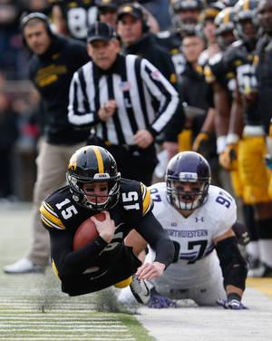 Photo - Iowa quarterback Jake Rudock (15) dives for a first down in front of Northwestern's Tyler Scott (97) during the first half of an NCAA college football game Saturday, Oct. 26, 2013, in Iowa City, Iowa.  (AP Photo/Brian Ray)