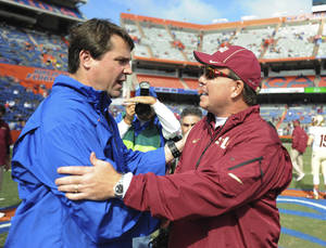 Photo - Florida coach Will Muschamp, left, meets with Florida State coach Jimbo Fisher, right prior the kick-off of an NCAA college football game Saturday, Nov. 30, 2013 in Gainesville, Fla. (AP Photo/Phil Sandlin)