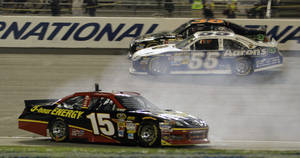 Photo -   Clint Bowyer (15) spins out in front of Martin Truex Jr., (55) and David Gilliland (38) during the NASCAR Sprint Cup Series auto race at the Richmond International Raceway in Richmond, Va., Sunday, Sept. 9, 2012. (AP Photo/Steve Helber)