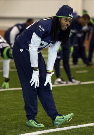 Photo - Seattle Seahawks cornerback Richard Sherman stretches at the start of NFL football practice Friday, Jan. 31, 2014, in East Rutherford, N.J. The Seahawks and the Denver Broncos are scheduled to play in the Super Bowl XLVIII football game Sunday, Feb. 2, 2014. (AP Photo/Jeff Roberson)