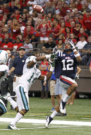 photo -   Mississippi wide receiver Donte Moncrief (12) reaches for a touchdown pass in front of Tulane cornerback Jordan Batiste (14) the first half of an NCAA college football game in New Orleans, Saturday, Sept. 22, 2012. (AP Photo/Bill Haber)