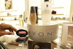 Photo - In this file photo, a saleswoman places items for display in an Avon store in New York. Struggling Avon Products Inc. is rejecting a buyout offer worth about $10 billion from beauty company Coty Inc. AP Photo