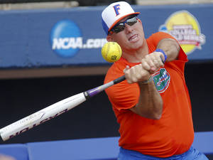 Photo - Florida coach Kenny Gajewski hits a ball during the Women's College World Series media day at ASA Hall of Fame Stadium on Wednesday, May 28, 2014 in Oklahoma City, Okla.  Photo by Chris Landsberger, The Oklahoman