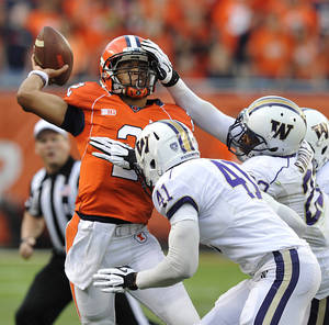 Photo - Illinois' Nathan Scheelhaase (2) gets defensive pressure from Washington's Travis Feeney (41) and Josh Shirley during the first half of an NCAA college football game Saturday, Sept. 14, 2013, in Chicago. (AP Photo/Jim Prisching)