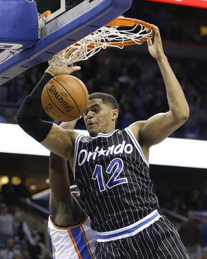 Photo - Orlando Magic's Tobias Harris (12) dunks the ball in front of Oklahoma City Thunder's Reggie Jackson at the buzzer to win an NBA basketball game 103-102 in Orlando, Fla., Friday, Feb. 7, 2014. (AP Photo/John Raoux)