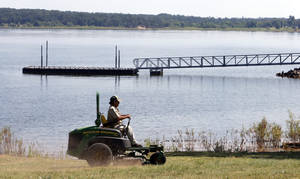 Photo -  Tony Palmer mows Wednesday at Lake Thunderbird State Park in Norman ahead of the Labor Day holiday weekend. Photo by Steve Sisney, The Oklahoman  <strong>Steve Sisney -  STEVE SISNEY </strong>