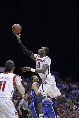 Photo - Louisville's Gorgui Dieng (10) puts up a shot against Duke during the second half of the Midwest Regional final in the NCAA college basketball tournament, Sunday, March 31, 2013, in Indianapolis. (AP Photo/Darron Cummings) <strong>Darron Cummings</strong>