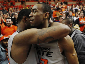 Photo - Oklahoma State senior guard Markel Brown (right) hugs teammate Marcus Smart (left) after an NCAA college basketball game between Oklahoma State University (OSU) and Kansas State held in Gallagher-Iba Arena in Stillwater, Okla., Monday, March 3, 2014. Oklahoma State defeated Kansas State 77-61.  Photo by KT King/ For The Oklahoman