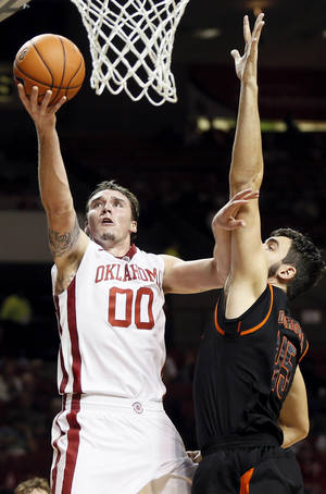 Photo - Oklahoma's Ryan Spangler (00) takes the ball to the hoop against Mercer's Monty Brown (45) during an NCAA men's college basketball game between the Oklahoma Sooners (OU) and the Mercer Bears at Lloyd Noble Center in Norman, Okla., Monday, Dec. 2, 2013. Photo by Nate Billings, The Oklahoman