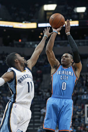 Photo - Oklahoma City Thunder's Russell Westbrook (0) shoots over Memphis Grizzlies' Mike Conley (11) in the first half of an NBA basketball game in Memphis, Tenn., Wednesday, Dec. 11, 2013. The Thunder defeated the Grizzlies 116-100. (AP Photo/Danny Johnston)