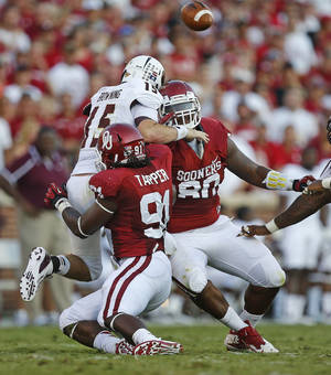 Photo - Oklahoma's Charles Tapper (91) and Jordan Phillips (80) hit Louisiana Monroe's Kolton Browning (15) as he throws during a college football game between the University of Oklahoma Sooners (OU) and the University of Louisiana Monroe Warhawks at Gaylord Family-Oklahoma Memorial Stadium in Norman, Okla., on Saturday, Aug. 31, 2013. Oklahoma won 34-0. Photo by Bryan Terry The Oklahoman