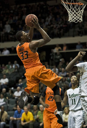 Photo - South Florida's Anthony Collins (11) watches as Oklahoma State' Marcus Smart (33) shoots during the first half of an NCAA college basketball game Monday, Nov. 25, 2013, in Tampa, Fla. (AP Photo/Steve Nesius)