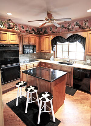 Photo - Holstein-patterned stools add a touch of whimsy to the kitchen island at 1600 Kingsgate in Yukon.  Photo by David McDaniel, The Oklahoman