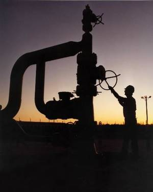Photo - An undated photo provided by the Energy Department shows a silhouetted technician working on one of the Reserve's wellheads at an undisclosed location on the U.S. Gulf Coast. The United States' emergency fuel tank -- the Strategic Petroleum Reserve    is almost full for the first time since its creation about 30 years ago. (AP Photo/Energy Department)