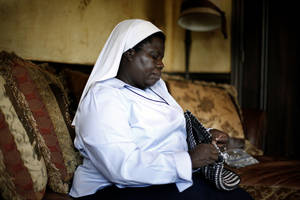 photo - Sister Rosemary Nyirumbe sews a strap onto a pop-tab purse Tuesday at the home of Reggie and Rachelle Whitten of Oklahoma City.  <strong>SARAH PHIPPS - SARAH PHIPPS</strong>