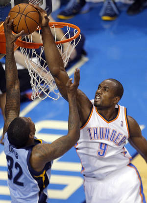 Photo - Oklahoma City's Serge Ibaka (9) blocks the shot of Memphis' Ed Davis (32) during Game 2 in the first round of the NBA playoffs between the Oklahoma City Thunder and the Memphis Grizzlies at Chesapeake Energy Arena in Oklahoma City, Monday, April 21, 2014. Photo by Sarah Phipps, The Oklahoman