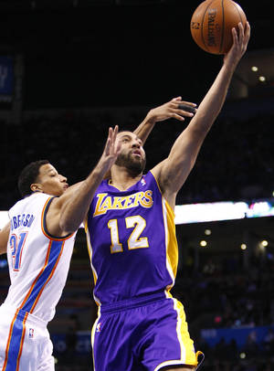 Photo - Los Angeles Lakers guard Kendall Marshall (12) goes to the basket in front of Oklahoma City Thunder guard Andre Roberson (21) during the first quarter of an NBA basketball game in Oklahoma City, Thursday, March 13, 2014. (AP Photo/Alonzo Adams)