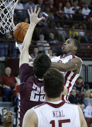 Photo - Oklahoma  guard Buddy Hield (24) shoots in front of Oklahoma Christian's John Moon (25) in the second half of an NCAA college basketball exhibition game in Norman, Okla., Monday, Nov. 4, 2013. Oklahoma won 88-76. (AP Photo/Sue Ogrocki)