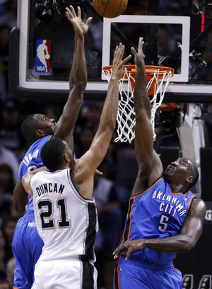 Photo - Oklahoma City's Serge Ibaka (9) and Kendrick Perkins (5) defend against San Antonio's Tim Duncan (21) during Game 5 of the Western Conference Finals in the NBA playoffs between the Oklahoma City Thunder and the San Antonio Spurs at the AT&T Center in San Antonio, Thursday, May 29, 2014. Photo by Sarah Phipps, The Oklahoman
