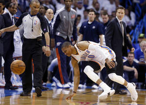 Photo - In this photo taken Wednesday, April 24, 2013, Oklahoma City Thunder guard Russell Westbrook stumbles after injuring his right knee in the second quarter of Game 2 of a first-round NBA basketball playoff series against the Houston Rockets in Oklahoma City. Westbrook, who remained in the game, will have surgery to repair a torn meniscus in his right knee and be out indefinitely, dealing a harsh blow to the City Thunder's championship chances. (AP Photo/Sue Ogrocki)