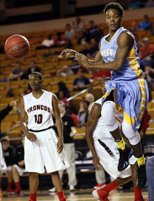 Photo - Putnam City West's Omega Harris, right, passes the ball during the Patriots' Class 6A state semifinal victory over Mustang.