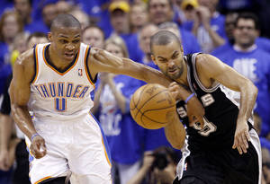 Photo - Oklahoma City's Russell Westbrook, left, attempts to steal from San Antonio's Tony Parker during Game 3 of the Western Conference Finals at the Chesapeake Energy Arena on Thursday. Photo by Sarah Phipps, The Oklahoman