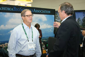 Photo -  Tommy Harlan, left, founder and CEO of Austin, Texas-based Emergent Technologies greets visitors Thursday at the OKBio exhibition booth at the 2014 BIO show in San Diego.  Photo by Jim Stafford, For The Oklahoman  <strong> -  photo by Jim Stafford </strong>
