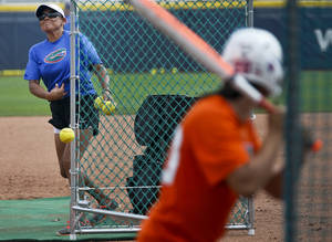 Photo - Florida coach Jennifer Rocha throws a pitch while in team practice during the Women's College World Series media day at ASA Hall of Fame Stadium on Wednesday, May 28, 2014 in Oklahoma City, Okla.  Photo by Chris Landsberger, The Oklahoman