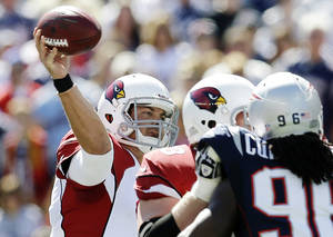 Photo -   Arizona Cardinals quarterback Kevin Kolb, left, passes over New England Patriots linebacker Jermaine Cunningham (96) in the first quarter of an NFL football game, Sunday, Sept. 16, 2012, in Foxborough, Mass. (AP Photo/Elise Amendola)
