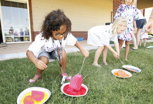 Photo - Five-year-olds Vanessa Fisher, left, and Olivia Frankenfield load up their flyswatters with paint Monday at the Edmond Multipurpose Activity Center. Photo By Paul Hellstern, The Oklahoman