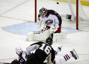 Photo - Pittsburgh Penguins' Brandon Sutter (16) puts the puck over Columbus Blue Jackets goalie Sergei Bobrovsky (72) and Fedor Tyutin (51) for a goal in the third period of a first-round NHL playoff hockey game in Pittsburgh Wednesday, April 16, 2014. The Penguins won 4-3, with Sutter's goal being the game-winner. (AP Photo/Gene J. Puskar)