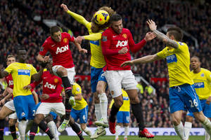 Photo - Manchester United's Robin van Persie, centre right, jumps for the ball against Newcastle's Fabrizio Coloccini, centre, during their English Premier League soccer match at Old Trafford Stadium, Manchester, England, Saturday Dec. 7, 2013. (AP Photo/Jon Super)