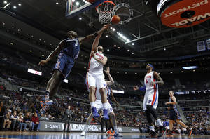Photo - Charlotte Bobcats' Bismack Biyombo (0) and Detroit Pistons' Josh Harrellson (55) reach for a rebound during the first half of an NBA basketball game in Auburn Hills, Mich., Friday, Dec. 20, 2013. (AP Photo/Paul Sancya)