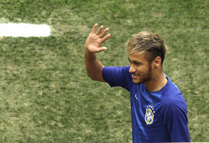 Photo - Brazil's Neymar waves as he enters the pitch to sit on the bench before the World Cup third-place soccer match between Brazil and the Netherlands at the Estadio Nacional in Brasilia, Brazil, Saturday, July 12, 2014. (AP Photo/Themba Hadebe)