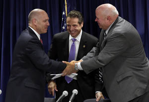 Photo - Anthony Simon, general chairman of the United Transportation Union, left, and Metropolitan Transportation Authority Chairman Thomas Prendergast, right, shake hands in front of Gov. Andrew Cuomo after a tentative labor agreement was reached at Cuomo's office in New York on Thursday, July 17, 2014. (AP Photo/Richard Drew)