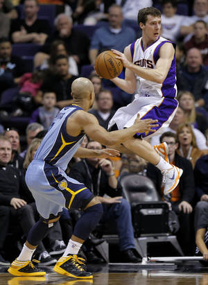 photo - Memphis Grizzlies' Jerryd Bayless defends as Phoenix Suns' Goran Dragic, right, looks to pass during the second half of an NBA basketball game, Sunday, Jan. 6, 2013, in Phoenix. (AP Photo/Matt York)