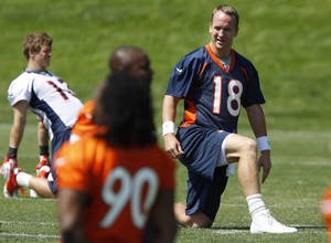 photo -   Denver Broncos quarterback Peyton Manning (18) stretches during an NFL football practice at the team's training facility in Englewood, Colo., on Thursday, June 14, 2012. (AP Photo/David Zalubowski)
