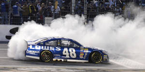 Photo - Jimmie Johnson (48) burns his tires after winning the NASCAR Sprint Cup series auto race at Texas Motor Speedway in Fort Worth, Texas, Sunday, Nov. 3, 2013. (AP Photo/Larry Papke)