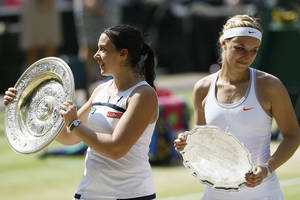 Photo - Marion Bartoli of France, left, and Sabine Lisicki of Germany pose during the trophy ceremony after Bartoli won the Women's singles final match against at the All England Lawn Tennis Championships in Wimbledon, London, Saturday, July 6, 2013. (AP Photo/Kirsty Wigglesworth)