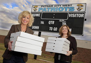photo - Putnam City West High School Patriots' community supporters Kerrie Frazier and Kim Banz at the school's football field holding pizza boxes Wednesday. Oct. 27, 2010. Photo by Paul B. Southerland, The Oklahoman