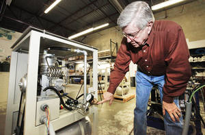 photo - Ron Peeler, with HYPRES Equipment, demonstrates a home-fueling system for compressed natural gas vehicles. Photos By David McDaniel, The Oklahoman